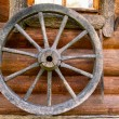 Hand spinning wheel on  wall of  old log house in the Russian village. — Stock Photo #52885161