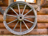 Hand spinning wheel on  wall of  old log house in the Russian village. — Stock Photo