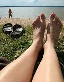 Closeup image of legs senior  sitting relaxed on sandy beach. — Stock Photo