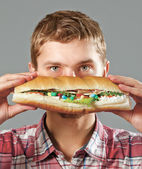 Hungry young man with a tasty hot dog and pills, isolated on grey — Stock Photo