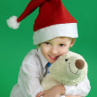 Little boy wearing a christmas hat and holding  toy, green background — Stock Photo #72957459