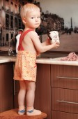 Portrait of a child holding a cup at the kitchen — Stock Photo