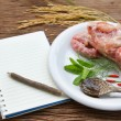 Notebook for recipes and raw chicken bone with spices on wooden — Stock Photo #56964123