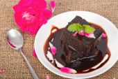 Chocolate brownie on plate with rose petals — Stock Photo