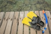 Scuba mask with yellow flippers on wooden pier background — Stock Photo