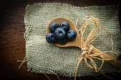 Blueberries on a Spoon with Burlap Woven Background — Stock Photo
