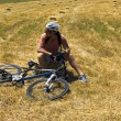 Cyclist man is resting on hay bale in a field — Stock Photo #75832583