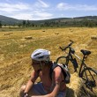 Cyclist man is resting on hay bale in a field — Stock Photo #75832969