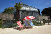 Striped deckchairs and umbrella on a sand — Stock Photo