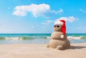 Christmas snowman in santa hat at sandy beach — Stock Photo