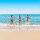 Women in Christmas hats on sea beach — Stock Photo
