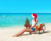 Woman at sea beach in santa hat sitting at sled — Stock Photo