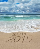 Happy New Year 2015 wash away 2014 concept on sea beach — Stock Photo
