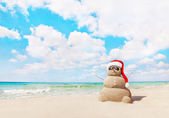 Sandy snowman in santa hat on sea beach — Zdjęcie stockowe