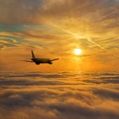 Airplane above stratum of sunset clouds — Stock Photo
