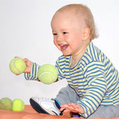 Happy baby plays with tennis balls — Stock Photo