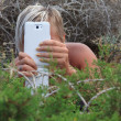A girl with smart phone hiding in the bushes outdoors — Stock Photo #58340099