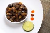 Une plaque avec des moules non cuites et de la chaux avec des sauces sur une natte brune — Photo