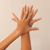 Close-up of female hands in oil on beige background — Stock Photo