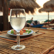 Beach evening on the sunset with glass of water and dinner — Stock Photo #67894469