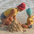 Mother and daughter building sandcastle on the beach — Stock Photo #68572017