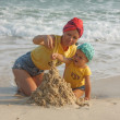 Mother and daughter building sandcastle on the beach — Stock Photo #68572205