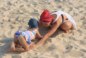 Young mother playing with daughter on beach — Stock Photo
