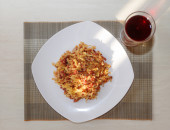 Pasta with fried meat on white plate and glass of juice — Stock Photo