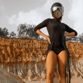 Biker girl in hemlet standing in desert land — Stock Photo
