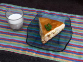 Chicken and potato pie segment with glass of milkt against black marble background — Stock Photo