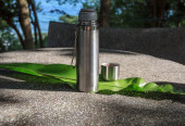 Open thermos on a stone table — Stock Photo