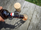 Frothy dark beer pouring into tall glasses from a brown glass bottle in summer garden on rustic wooden table — Stock Photo