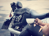 Woman drinking coffee with motorcycle — Stock Photo