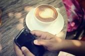 Vintage latte art coffee with smart phone — Zdjęcie stockowe