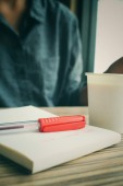 Woman with pen on paper and coffee cup — Stock Photo