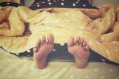 Feet in the bed — Stock Photo