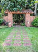 Loopbrug aan baksteen deuropening in groene tuin — Stockfoto