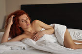 Red-haired girl lying in white bed — Stock Photo