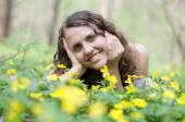 Smiling girl with big bouquet of spring flowers lying on green grass. Mothers day concept — Stock Photo