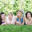 Group of happy smiling Teenage Students Outside lying on a grass — Stock Photo #72705543
