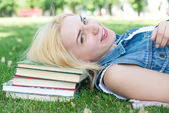 Beautiful smiling  young woman lying on grass and reading blue book, summer green park. Female student girl outside in park. Happy young university student of mixed European and Caucasian ethnicity. — Stock Photo