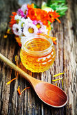 Fresh honey and flowers — Stock Photo