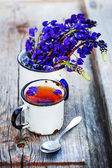 Cup of herbal tea and summer flowers — Stock Photo