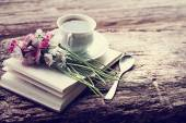 A cup of hot coffee, flowers and book. — Stockfoto
