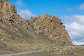 Track and rock hill through Iceland, blue sky — Photo