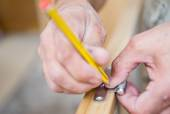 Closeup of carpenter with pencil working on door — Stock Photo