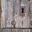 Front view of old lock and wooden door with iron nails — Stock Photo #57125675