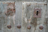 Old run-down wooden door and iron lock — Stock Photo