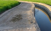Water canal, track and plantations — Stock Photo