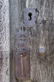 Old run-down wooden door and decorated iron lock — Stock Photo